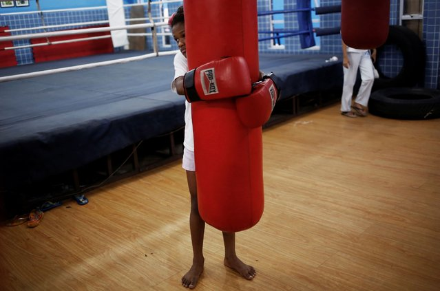 A girl embraces a punch bag during an exercise session at a boxing school, in the Mare favela of Rio de Janeiro. (Photo by Nacho Doce/Reuters)