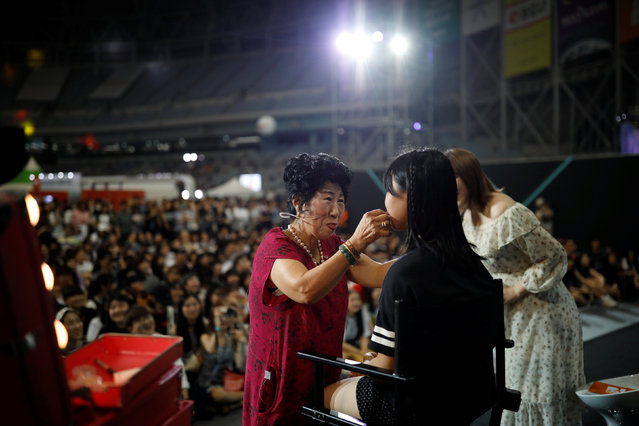 Park Mak-rye, a 70-year-old YouTuber, puts on makeup on a volunteer at a makeup show during DIA Festival in Seoul, South Korea, July 16, 2017. Park's videos are all about showing off her wrinkles and her elderly life in the raw. Young South Koreans find her so funny and adorable that big companies like Samsung Electronics and Lotte are banking on her popularity. But despite her new life as a celebrity, she still gets up before dawn to run her diner. (Photo by Kim Hong-Ji/Reuters)