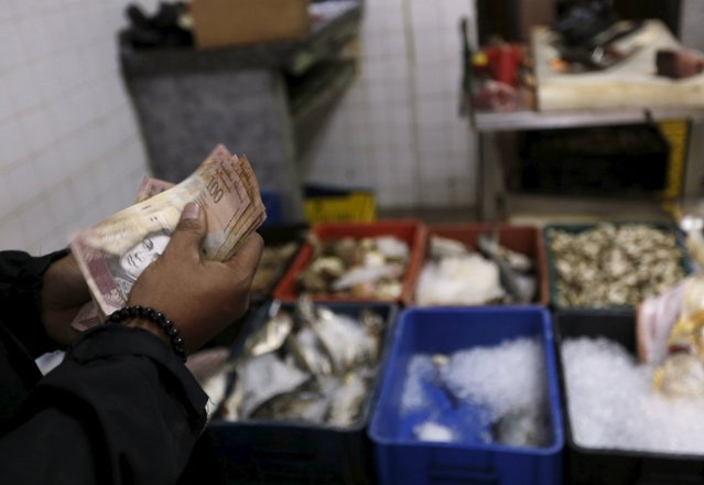 A customer counts his money before paying at a fish market in downtown Caracas, July 11, 2015. (Photo by Jorge Dan Lopez/Reuters)