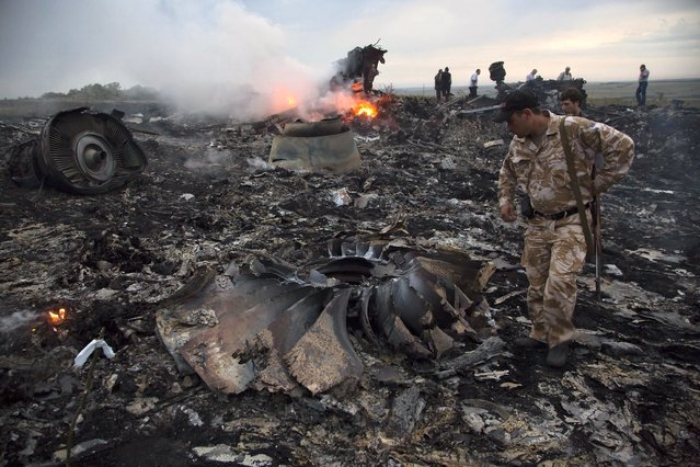 People walk amongst the debris at the crash site of a passenger plane near the village of Grabovo, Ukraine, Thursday, July 17, 2014. Ukraine said a passenger plane carrying 295 people was shot down Thursday as it flew over the country, and both the government and the pro-Russia separatists fighting in the region denied any responsibility for downing the plane. (Photo by Dmitry Lovetsky/AP Photo)