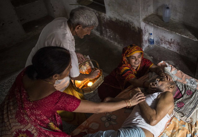 Kishore Pandey, 82, lies on a bed as his daughter, Usha Tiwari, holds him and a priest stands by them (L) at Mukti Bhavan (Salvation House) in Varanasi, in the northern Indian state of Uttar Pradesh, June 19, 2014. (Photo by Danish Siddiqui/Reuters)