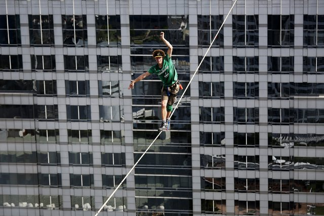 """Andy Lewis of the USA, also known as """"Mr. Slackline"""" walks on the thin slackline between buildings in central Bangkok July 23, 2014. Lewis walked the distance of 169 meters on a line set between a rooftop and the 55th floor of another building in just over an hour in what organizers said was the world record breaking free solo slacklining event. (Photo by Damir Sagolj/Reuters)"""