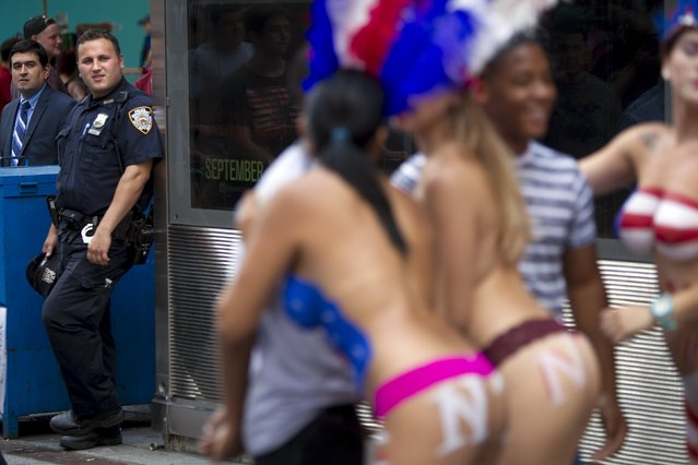 A policeman looks on as women who pose for tips wearing body paint and underwear are pictured in Times Square in New York, August 19, 2015. (Photo by Carlo Allegri/Reuters)