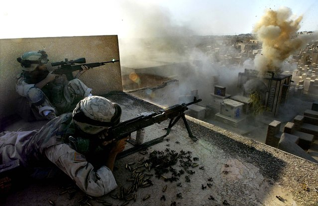 U.S. soldiers from Company C, First Battalion of the Fifth Cavalry Regiment on a rooftop in a cemetery as a round from a Bradley Fighting Vehicle hits a tomb where a sniper was suspected to be hiding, during the battle for Najaf on August 11, 2004