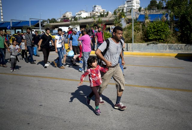"""A Syrian refugee man runs with a child as they try to catch a bus following their arrival onboard """"Eleftherios Venizelos"""" passenger ship at the port of Piraeus near Athens, Greece, August 20, 2015. (Photo by Stoyan Nenov/Reuters)"""