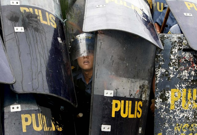 Police regroup themselves following a clash with protesters as the latter try to get closer to the Philippine Congress to protest the third State of the Nation address of Philippine President Benigno Aquino III, in suburban Quezon city, northeast of Manila on July 23, 2012. (Photo by Bullit Marquez/Associated Press)