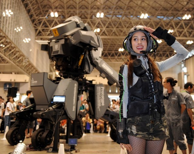 """Female """"pilot"""" Anna (R) salutes after demonstrating Japanese electronics company Suidobashi Heavy Industry's newly unveiled robot """"Kuratas"""" at the Wonder Festival in Chiba, suburban Tokyo on July 29, 2012. The Kuratas robot, which will go on sale with a price tag of one million USD, measures four meters in height, weighs four tons and has four wheeled legs that can either be controlled remotely through the 3G network or by a human seated within the cockpit."""