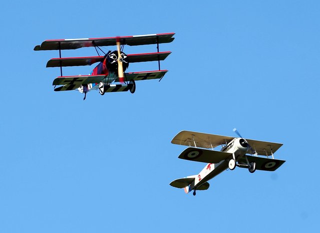 A World War 1-era Fokker DR-1 tri-plane and Spad VII bi-plane, both reproductions, perform a dog fight during an air show at the Old Rhinebeck Aerodrome on Sunday, July 6, 2014, in Rhinebeck, N.Y. (Photo by Mike Groll/AP Photo)
