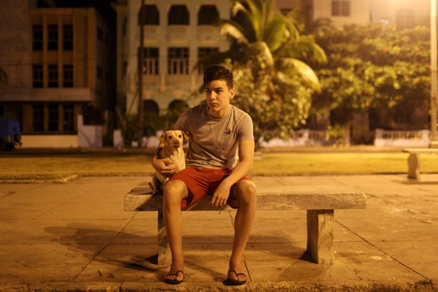 "Student Michael Figueredo, 17, sits with his dog ""Whiskey"" in Havana, March 1, 2015. (Photo by Alexandre Meneghini/Reuters)"
