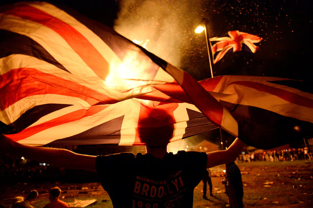 A boy holds a Union Jack flag in front of a bonfire burning in the Shankill Road area ahead of the Twelfth of July celebrations held by members of the Orange Order in Belfast, Northern Ireland, July 12, 2016. (Photo by Clodagh Kilcoyne/Reuters)