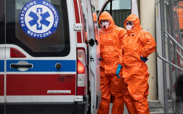 Medical staff in protective gear stand near an ambulance upon the arrival at the infectious ward of the Public Hospital in Lublin, Poland on March 12, 2020. (Photo by Jakub Orzechowski/Agencja Gazeta via Reuters)