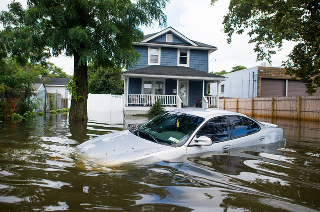 A car is abandoned on a flooded Reddington St. following heavy rains and flash flooding August 13, 2014 in Bayshore, New York. The south shore of Long Island along with the tri-state region saw record setting rain that caused roads to flood entrapping some motorists. (Photo by Andrew Theodorakis/Getty Images)
