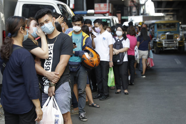 People wait along a street to buy protective face masks at a store in Manila, Philippines on Thursday, January 30, 2020. Health Secretary Francisco Duque confirmed the Philippines' first case of a new virus that has infected thousands in China. (Photo by Aaron Favila/AP Photo)
