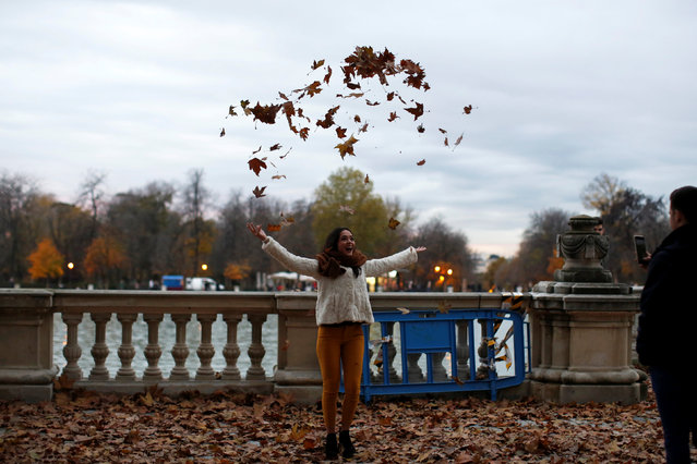 A woman plays with dry leaves in the Retiro park in central Madrid, Spain, December 5, 2016. (Photo by Juan Medina/Reuters)