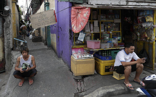 In this March 24, 2020, file photo, a sign that prohibits non-residents from entering the area is hung at the entrance of a slum area as two men sit outside while the city goes on enhanced community quarantine to prevent the spread of the new coronavirus in Metro Manila, Philippines. (Photo by Aaron Favila/AP Photo/File)