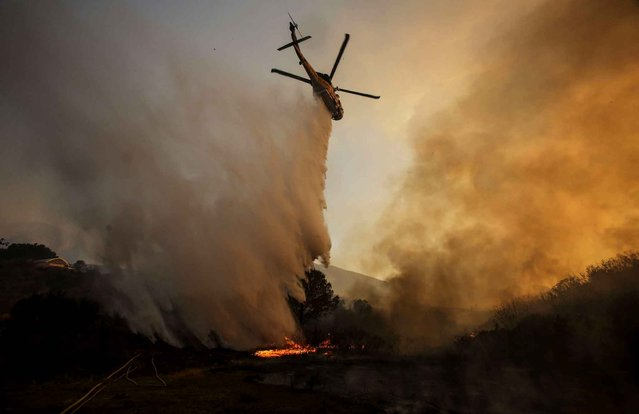 A helicopter maks a drop on a wildfire near Placenta Caynon Road in Santa Clarita, Calif., Sunday, July 24, 2016. Thousands of homes remained evacuated Sunday as two massive wildfires raged in tinder-dry California hills and canyons. (Photo by Ringo H.W. Chiu/AP Photo)