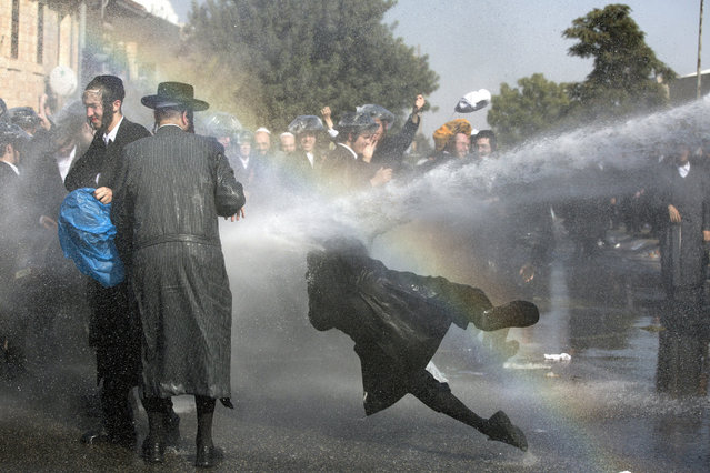 Israeli police use water cannon to disperse Ultra-Orthodox Jewish demonstrators blocking a main junction as they protest against army recruitment in Jerusalem, Israel, 17 September 2017. On 12 September, the Israeli Supreme Court rejected a goverment bill exempting Haredi service from the Israeli army. (Photo by Abir Sultan/EPA)