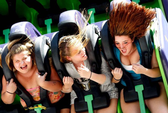 From left, friends Latisha Case, 16, Laurastina Coffman, 16, and Amber Neeman, 16, all of Roseburg, Ore. take a spin on a ride at the Douglas County Fair in Roseburg August 8, 2014. (Photo by AP Photos/The News-Review)