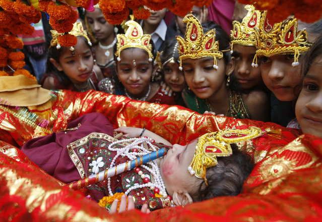 Schoolgirls dressed as Radha, the consort of Hindu Lord Krishna, look at a child dressed as Krishna during the celebrations to mark Janmashtami festival in Ahmedabad August 27, 2013. (Photo by Amit Dave/Reuters)