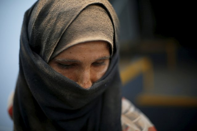 Syrian refugee woman covered with dust arrives at the Trabeel border, after she crossed into Jordanian territory with her family, near the northeastern Jordanian border with Syria, and Iraq, near the town of Ruwaished east of Amman September 10, 2015. (Photo by Muhammad Hamed/Reuters)