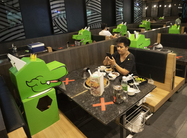 A customer uses a mobile phone while sitting with a cartoon dragon dolls the restaurant uses as space keepers for social distancing to help curb the spread of the coronavirus at shopping mall in Bangkok, Thailand, Monday, May 18, 2020. Thai authorities allowed department stores, shopping malls and other businesses to reopen from May 17, selectively easing restrictions meant to combat the coronavirus. (Photo by Sakchai Lalit/AP Photo)