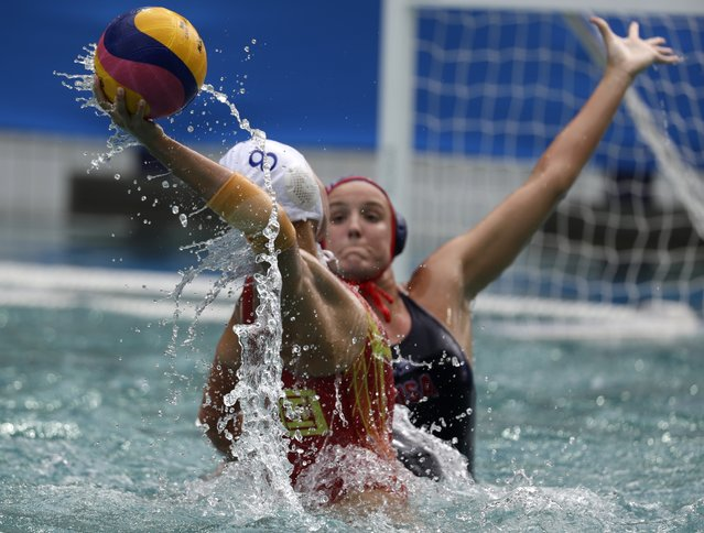 China's Cong Zhang, left, passes the ball forward as United States' KK Clark goes to block during their women's water polo preliminary round match at the 2016 Summer Olympics in Rio de Janeiro, Brazil, Thursday, August 11, 2016. (Photo by Sergei Grits/AP Photo)