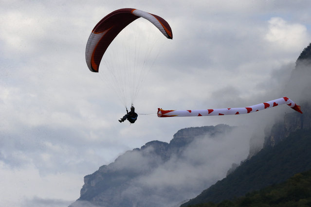 """A paraglider performs a demonstration flight during the 41st Icare Cup paragliding festival in Saint Hilaire du Touvet, French Alps, Saturday, September 20, 2014. The """"Coupe Icare"""" dedicated to free flight, orchestrates all the various types of flying such as hang gliding, paragliding and acrobatic sailplaneing. (Photo by Francois Mori/AP Photo)"""