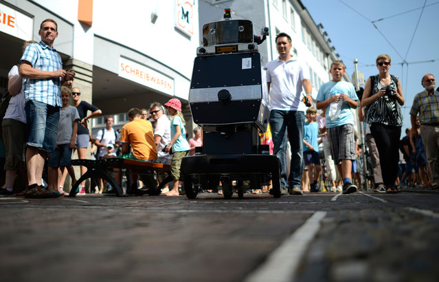 "The robot ""Obelix"" runs through Freiburg city center, on August 21, 2012. The machine, starting 9:45 in the morning at the University of Freiburg, found its way independently to a plaza in the center of Freiburg, about four kilometers away. Obelix made the journey, avoiding people and obstacles, in about 100 minutes. (Photo by Daniel Kopatsch/AP Photo)"