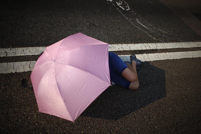 A protester sleeps under an umbrella as she blocks a street outside the government headquarters in Hong Kong September 30, 2014. (Photo by Carlos Barria/Reuters)