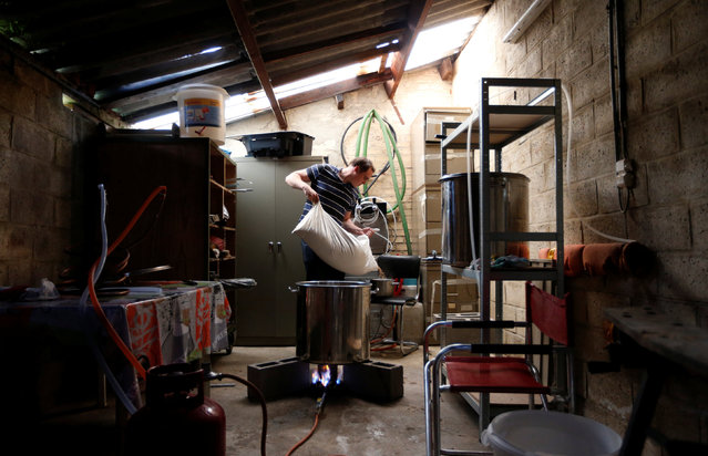 Jean-Christophe Larsimont, Vice President of the Belgian Homebrewers association, pours malt as he starts making his own beer in the garage of his house in Sambreville, Belgium, August 9, 2016. (Photo by Francois Lenoir/Reuters)