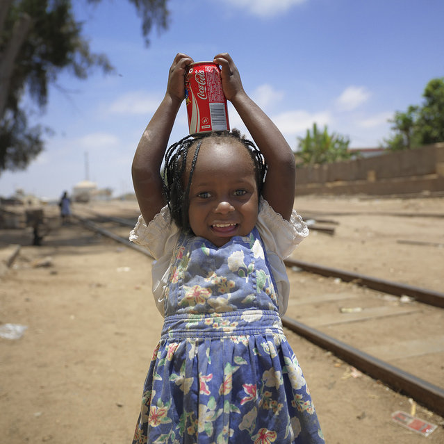 """Bringing back home the essential – Namibe Angola. This little girl was carrying on her head a Coca Cola bottle, back from the shop, like all the girls and women do in Angola"". (Eric Lafforgue)"