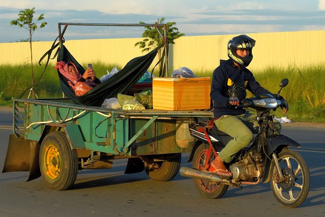 A man rides a motorbike pulling a trailer with a woman relaxing in a hammock, checking her phone, on a street in Phnom Penh, Cambodia on June 12, 2020. (Photo by Tang Chhin Sothy/AFP Photo)