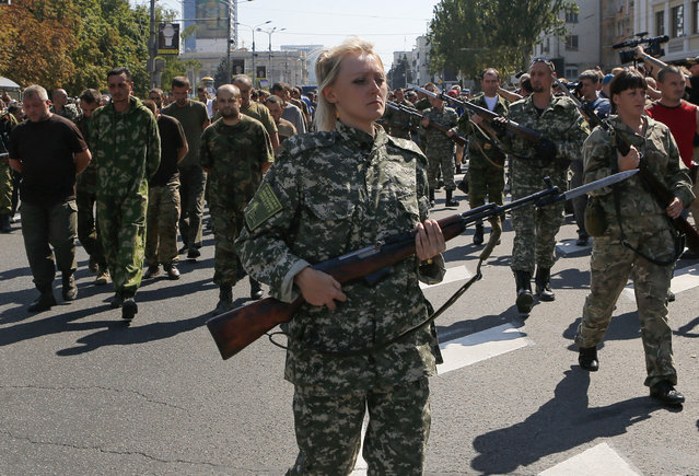 Armed pro-Russian separatists escort a column of Ukrainian prisoners of war as they walk across central Donetsk August 24, 2014. (Photo by Maxim Shemetov/Reuters)