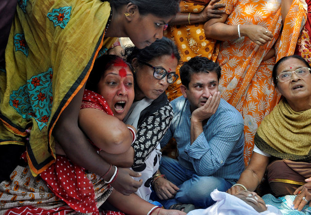 Shima (in red) mourns next to the body of her husband Sudip Datta Bhowmik, a local journalist, who according to local media was shot dead by a Tripura State Rifles trooper on Tuesday, in Agartala, India, November 22, 2017. (Photo by Jayanta Dey/Reuters)