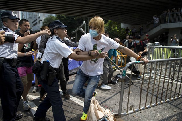 Police try to stop a masked anti-Occupy Central protester as he attempts to remove road blocks set up by pro-democracy protesters in the Central financial district in Hong Kong October 13, 2014. (Photo by Tyrone Siu/Reuters)