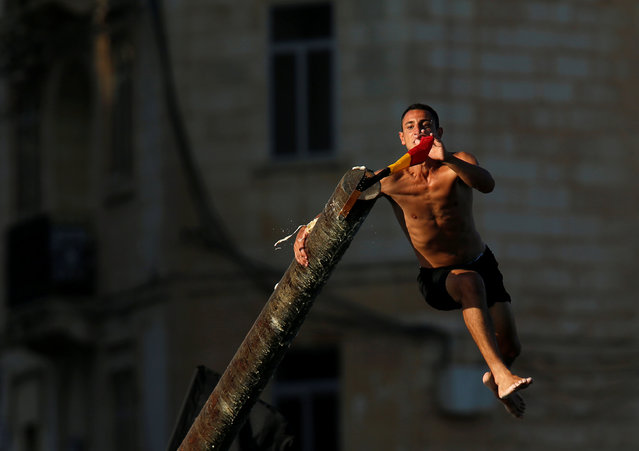 """A man tries to grab a flag on the """"gostra"""", a pole covered in grease, during the religious feast of St Julian, patron of the town of St Julian's, outside Valletta, Malta, August 28, 2016. In the traditional """"gostra"""", a game stretching back to the Middle Ages, young men, women and children have to make their way to the top and try to uproot one of the flags to win prizes. From May to September in Malta, there is hardly any weekend when a town or a village is not celebrating the feast of its patron saint or other saints revered in different churches. (Photo by Darrin Zammit Lupi/Reuters)"""