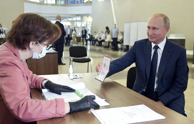Russian President Vladimir Putin shows his passport to a member of an election commission as he arrives to take part in voting at a polling station in Moscow, Russia, Wednesday, July 1, 2020. The vote on the constitutional amendments that would reset the clock on Russian President Vladimir Putin's tenure and enable him to serve two more six-year terms is set to wrap up Wednesday. (Photo by Alexei Druzhinin, Sputnik, Kremlin Pool Photo via AP Photo)