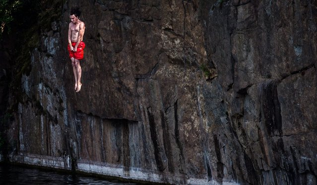 A man dives off a 10 meter cliff at flooded granite quarr near village of Hrimezdice, during hot summer day in central Bohemia, Czech Republic, 28 August 2016. (Photo by Filip Singer/EPA)