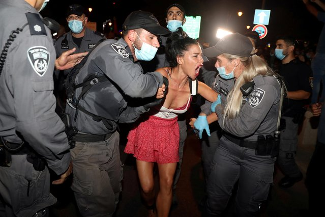 Police detain a woman during a protest against Prime Minister Benjamin Netanyahu and his government's handling of the coronavirus disease (COVID-19) crisis, near Netanyahu's residence in Jerusalem on July 24, 2020. (Photo by Ammar Awad/Reuters)