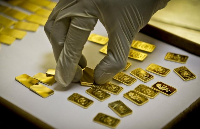 A gold press operator collects 10 gram gold blanks to press them with the logo of the Emirates Gold company in Dubai, United Arab Emirates. Gold prices remained relatively steady in 2012, close to $1,700 an ounce. (Photo by Kamran Jebreili/AP Photo)