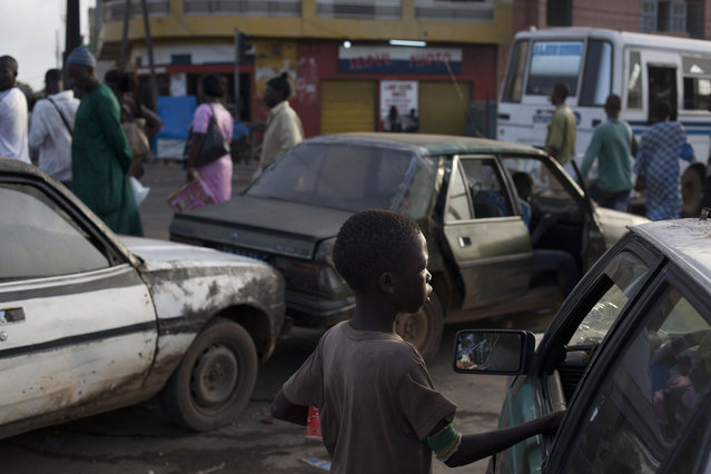 In this September 24, 2013 photo, a talibe begs for change from a driver stopped at a gas station, in the Medina Gounass suburb of Dakar, Senegal. (Photo by Rebecca Blackwell/AP Photo)