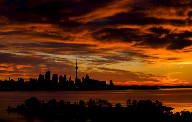 The sun begins to rise over the skyline in Toronto, September 21, 2015. (Photo by Mark Blinch/Reuters)