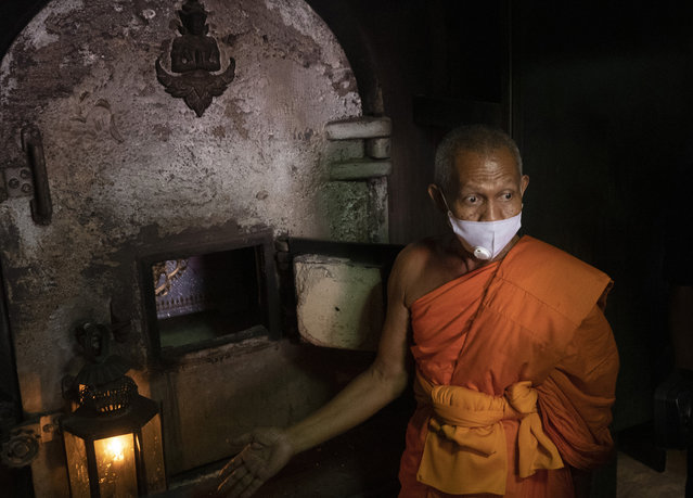 A Buddhist monk talks to media after putting the coffin of the infamous Si Ouey into an incinerator for cremation at Wat Bang Phraek Tai temple Nonthaburi province, Thailand, Thursday, July 23, 2020. The corpse of Si Ouey, a notorious figure who was convicted of murder in 1959 and accused of cannibalism, was put on museum display for six decades, but an online campaign last year was successful in having him be given a proper funeral. (Photo by Sakchai Lalit/AP Photo)
