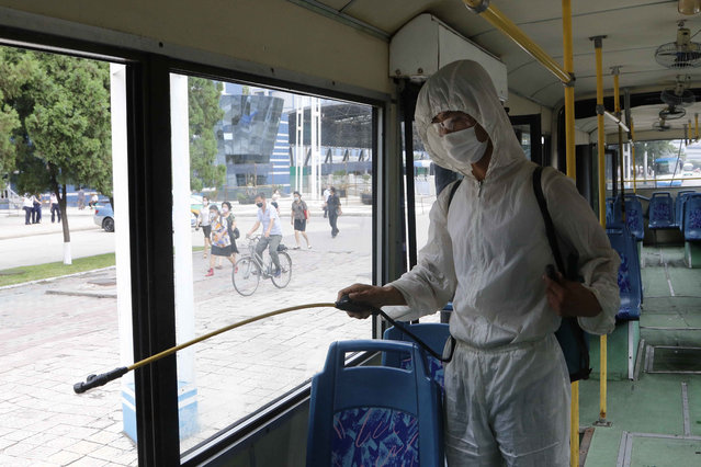 A man in a protective suit disinfects the inside of a trolley bus to help curb the spread of the coronavirus in Pyongyang, North Korea, Thursday, August 13, 2020. (Photo by Jon Chol Jin/AP Photo)