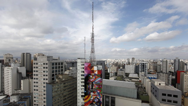 Brazilian graffiti artist Eduardo Kobra (C) puts the final touches to his piece of art in tribute to Brazilian architect Oscar Niemeyer, next to his assistants, at the financial center on Sao Paulo's Avenida Paulista January 22, 2013. Kobra created the 56-metre (61-yard) tall graffiti artwork as a tribute to Niemeyer, one of the 20th century's most influential modernist architects. Niemeyer died in December 2012, aged 104. REUTERS/Nacho Doce (BRAZIL - Tags: SOCIETY CITYSCAPE)