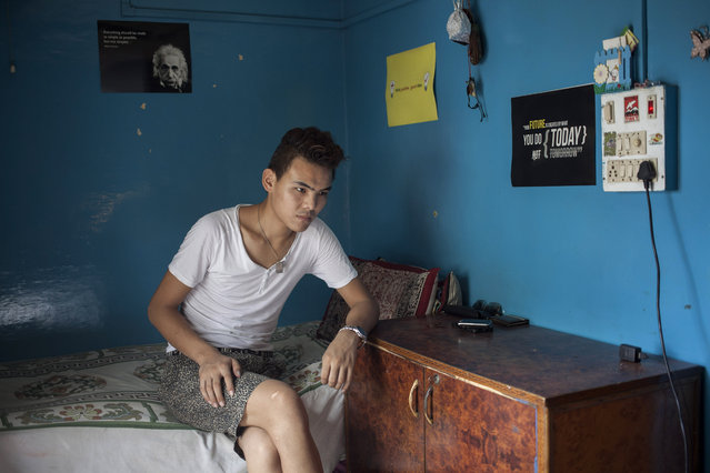 In this Wednesday, July 30, 2014 photo, Tibetan exile Kalsang Tsering, 20, sits in his room in New Delhi, India. Tsering said he missed his family when he was ill and in hospital with nobody to care for him. He now rents a room from a woman who treats him like a son and says the feeling of being cared for is wonderful. (Photo by Tsering Topgyal/AP Photo)