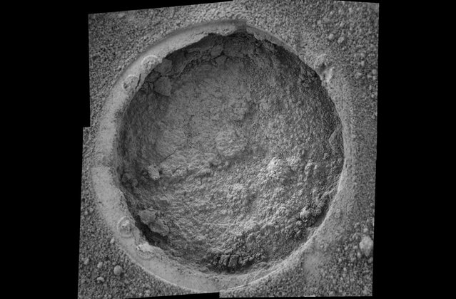 "This image taken by Opportunity shows a target dubbed ""Campbell"" on a rock called ""MacKenzie"" in ""Endurance Crater"". Opportunity dug a hole into the target with its rock abrasion tool, then captured this picture with its microscopic imager on sol 184 (July 30, 2004). The image mosaic is about 6 centimeters (2.4 inches) across. (Photo by NASA/JPL/Cornell/USGS/The Atlantic)"
