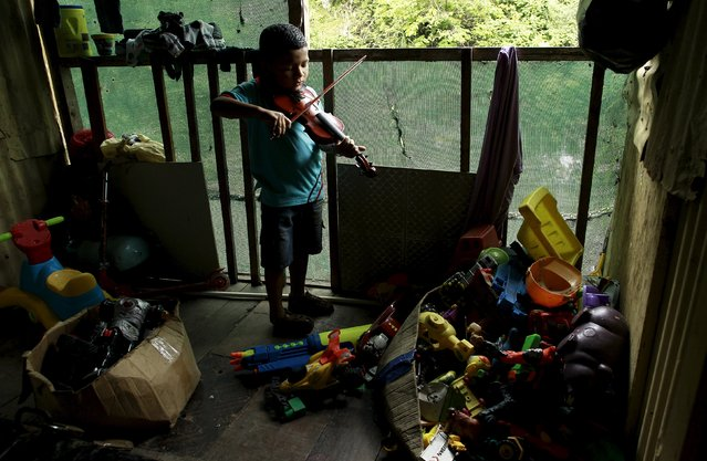 Ruben Escoriano, 6, practices in his house before his fiddle lesson at the Integral System of Artistic Education for Social Inclusion (SIFAIS) center in the poor neighborhood of La Carpio, Costa Rica October 8, 2015. (Photo by Juan Carlos Ulate/Reuters)