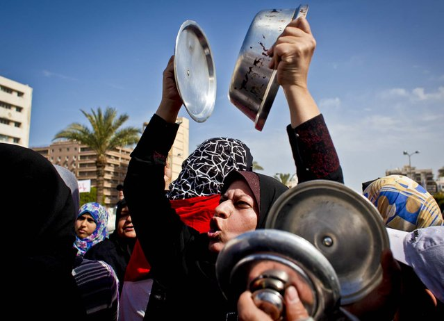 Women clang cooking pots together and chant anti-president Mohammed Morsi slogans while protesting in front of the provincial government headquarters on the six day day of a general strike, in Port Said, Egypt, February 22, 2013. Factory workers, activists and laborers have held street rallies throughout the northern tip along the Suez Canal. (Photo by Nasser Nasser/Associated Press)