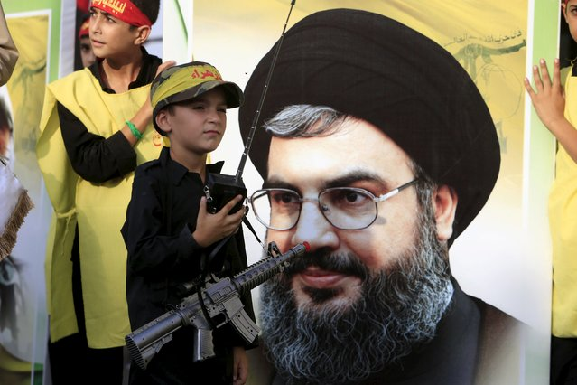 A Muslim Shi'ite boy carries a toy gun while standing next to a picture of Hezbollah leader Sayyed Hassan Nasrallah as he takes part in a march organised by Hezbollah during a re-enactment of the battle of Kerbala during a mourning process, ahead of the day of Ashura, in Saksakieh village, southern Lebanon, October 18, 2015. (Photo by Ali Hashisho/Reuters)
